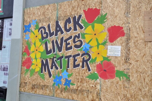 Black Lives Matter surrounded by flowers on a boarded up building