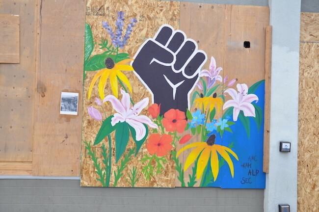 Black Lives Matter fist on side of boarded up building
