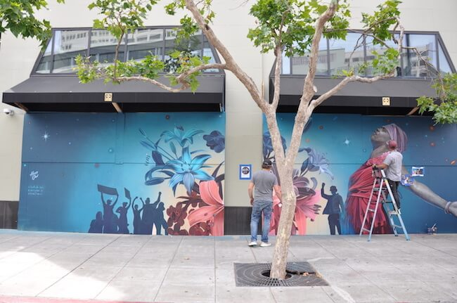 People painting racial justice mural on side of building