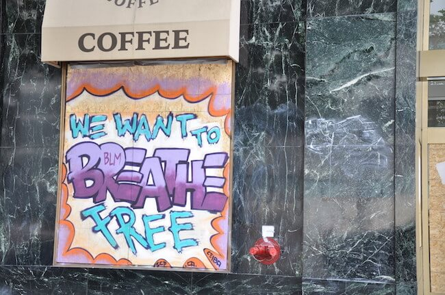 Black Lives Matter mural on the side of a boarded up coffee shop