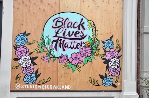 Black Lives Matter mural on the side of a boarded up building