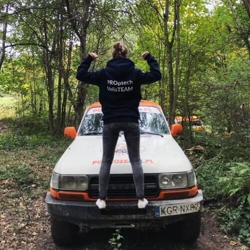 Woman standing on the bumper of the off-road car in the forest