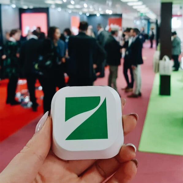 A female hand holding a beacon with a green Singu logo