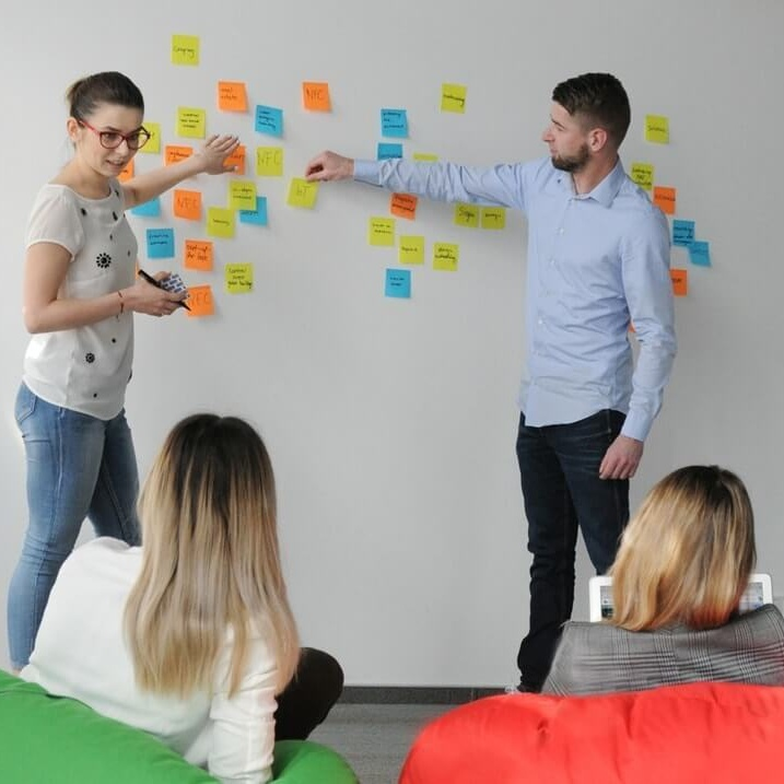 Woman and man presenting thoughts on sticky notes in front of a sitting audience in the office
