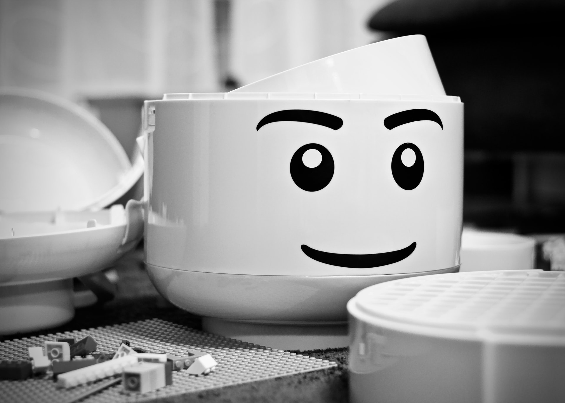 A greyscale photo of a large lego-person's head with the top taken off