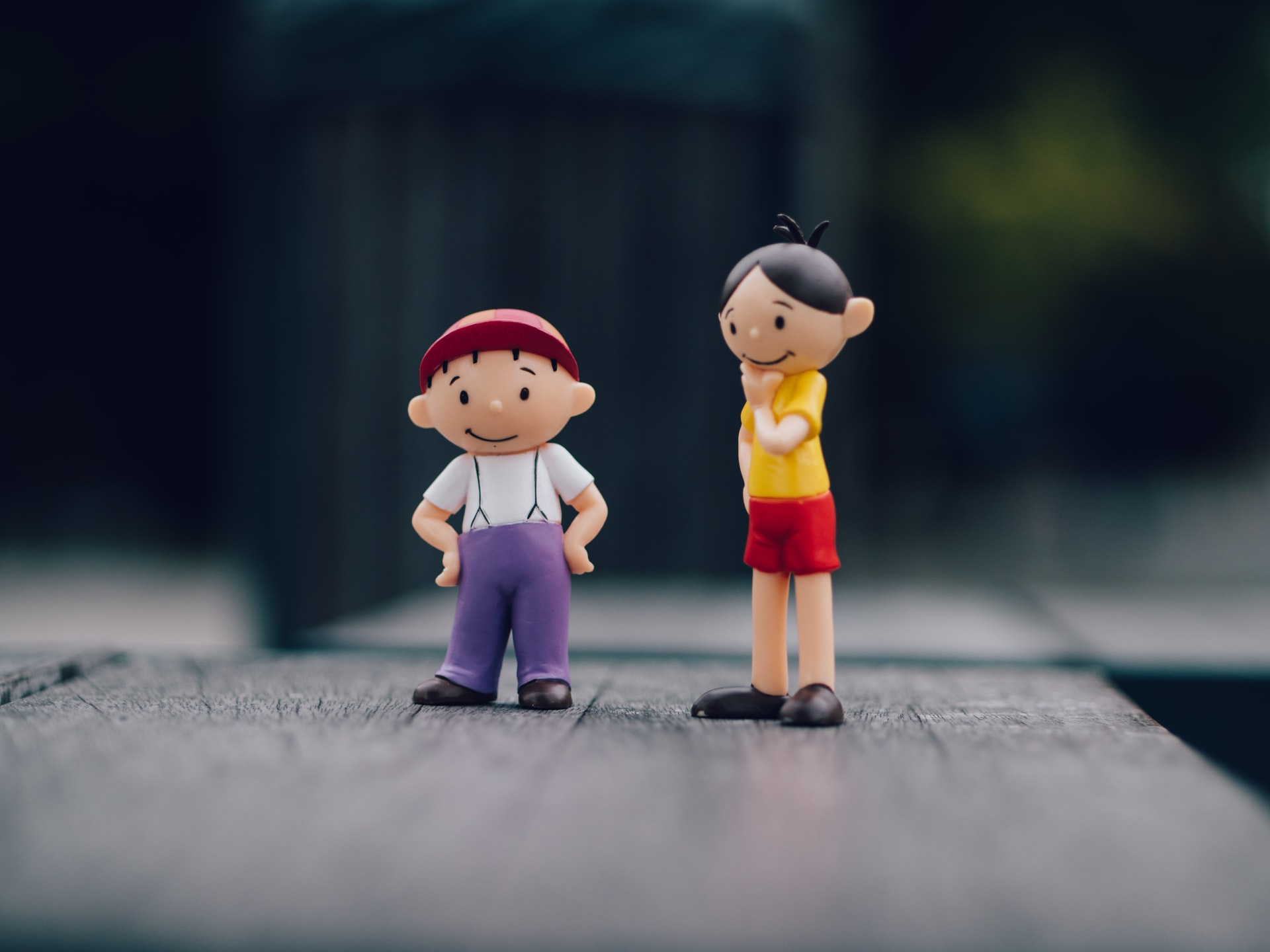 A shallow-focus image of two toy figures standing next to one another