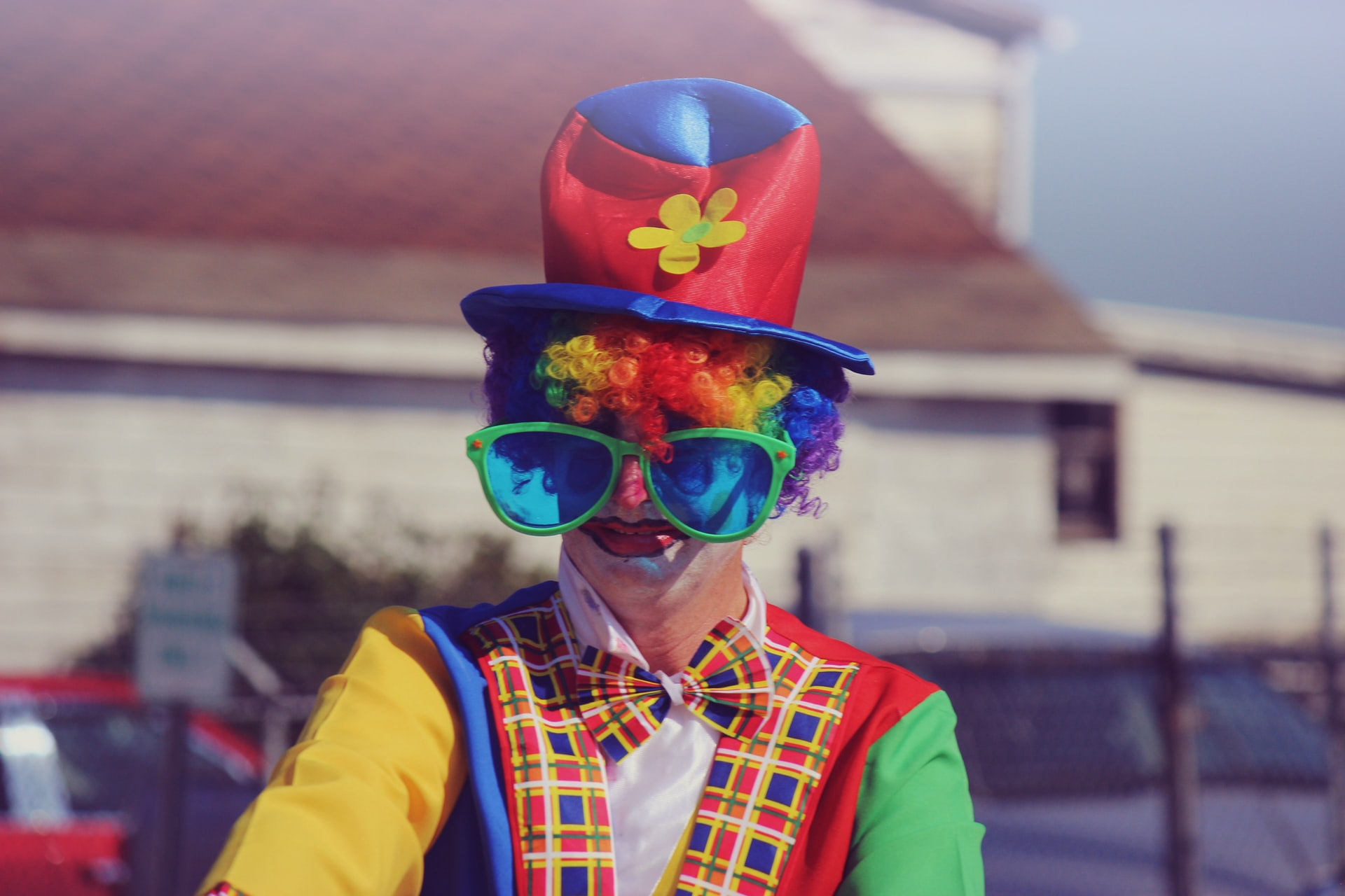 A portrait of a clown wearing a tall hat, huge glasses, and colorful clothes