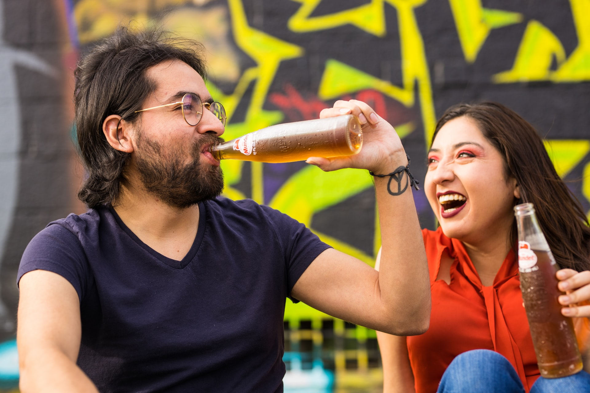 A photo of a couple. One person is drinking out of a glass bottle while the other laughs