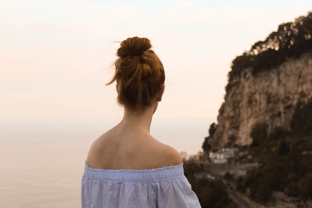 An image of a person looking out over the ocean and some cliffs