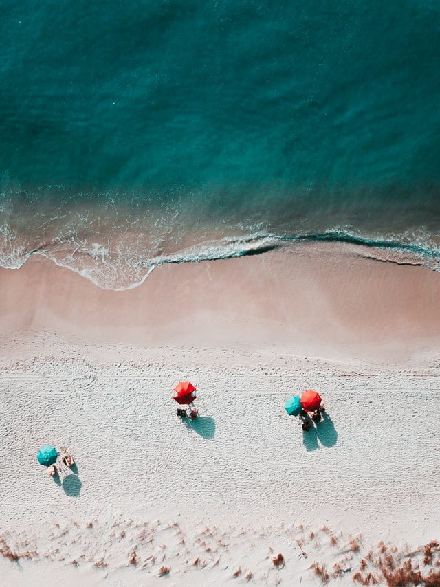 An aerial image of a shoreline with some people sitting on the beach