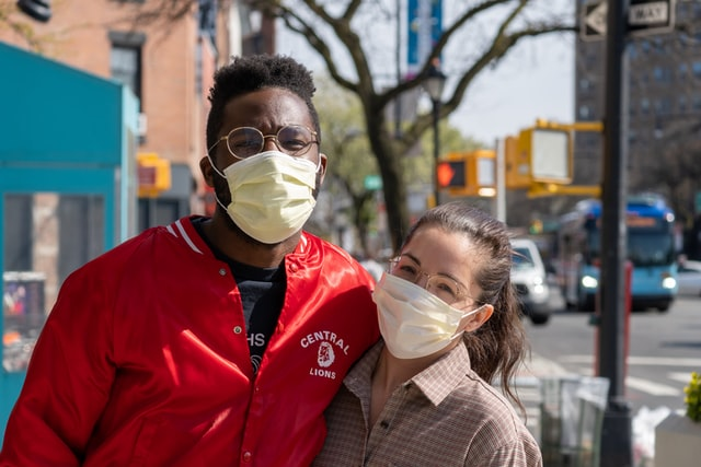 An image of a couple wearing medical masks outside