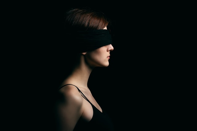 A photo of a person wearing a blindfold in a dark room