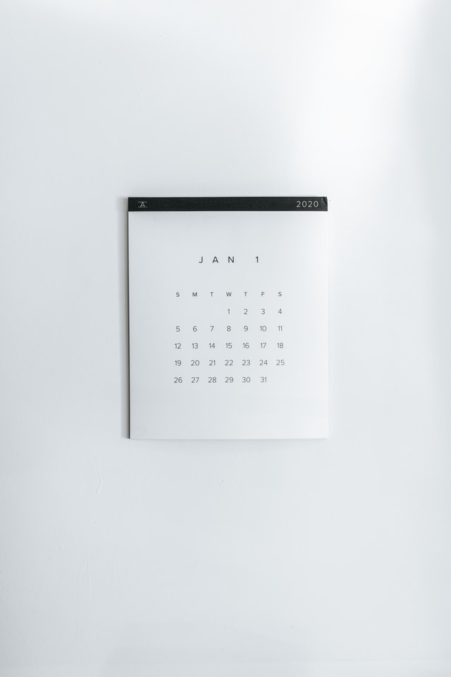 A very boring image of a white calendar hanging on a white wall.