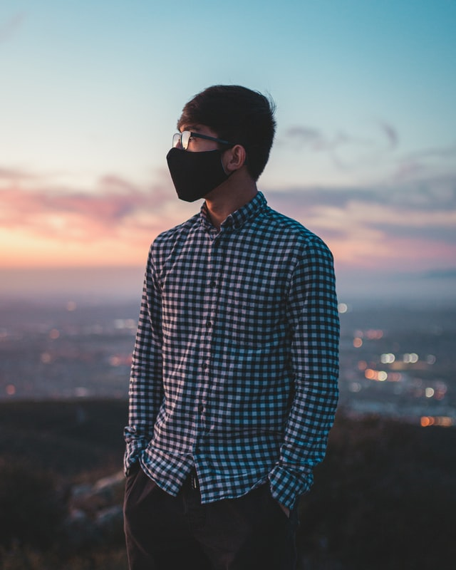 A person wearing a mask looks out into the distance