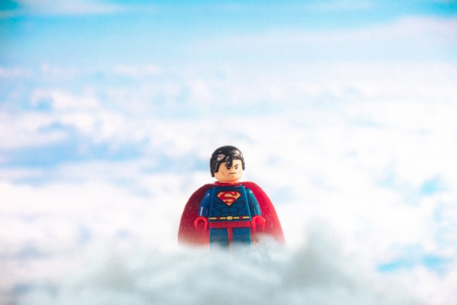 A lego figure of Superman floating above the clouds.