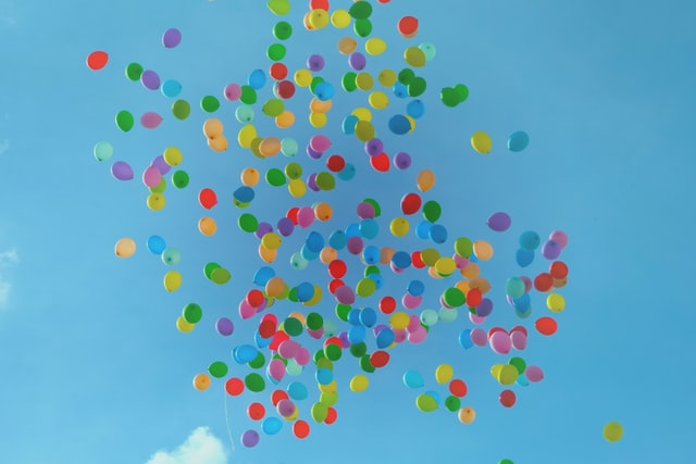 Many balloons of all colors float untethered in a blue sky.