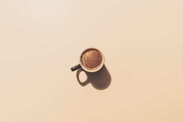 Looking down on a mug of coffee on a beige background.