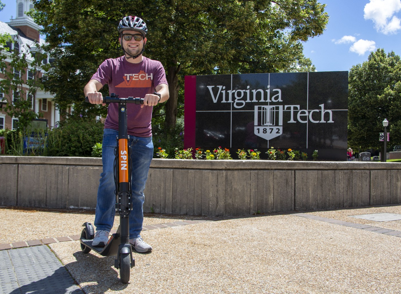 Man on Spin scooter in front of Virginia Tech