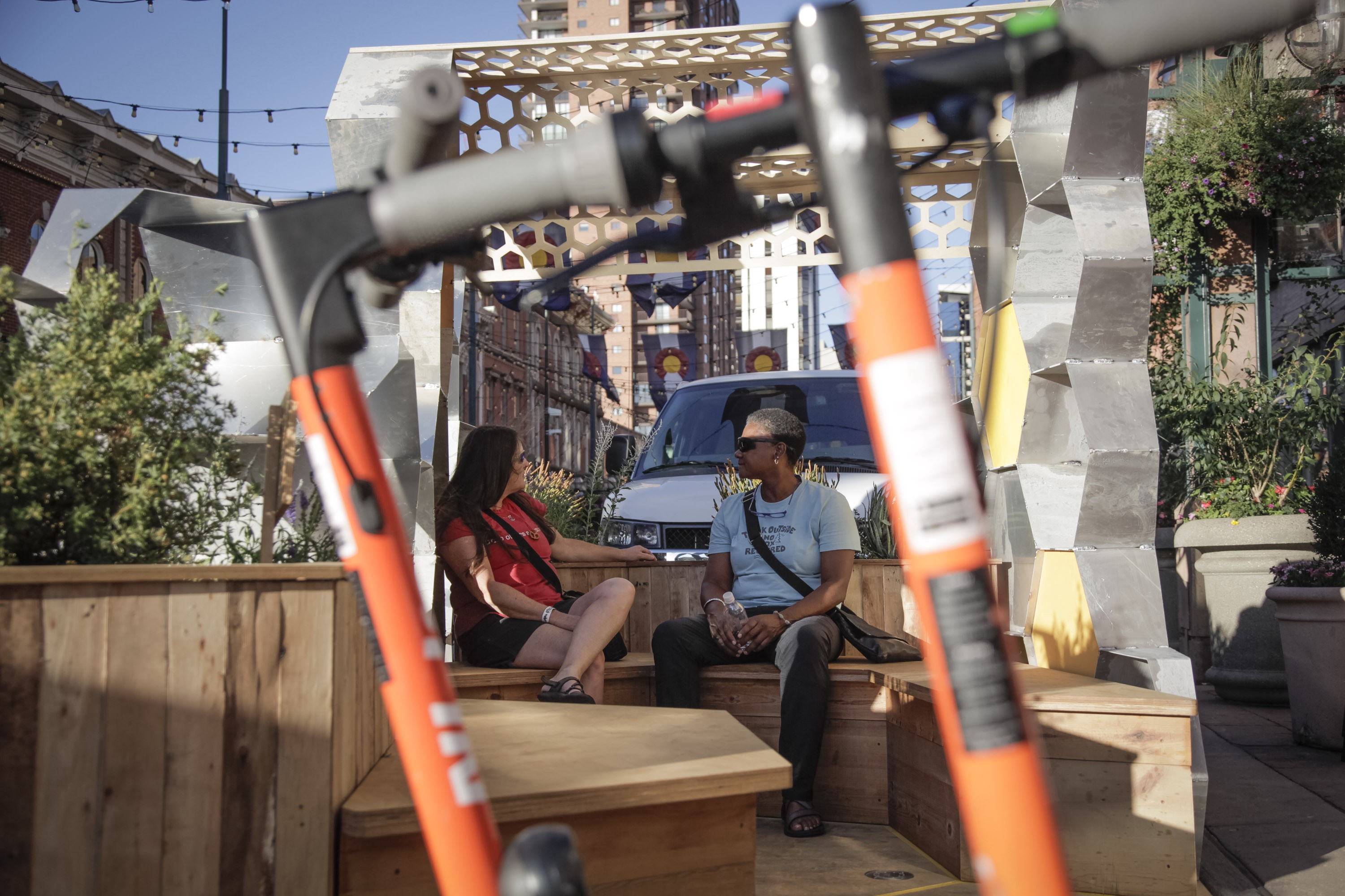Man and woman sitting inside honeycomb parklet with Spin scooters
