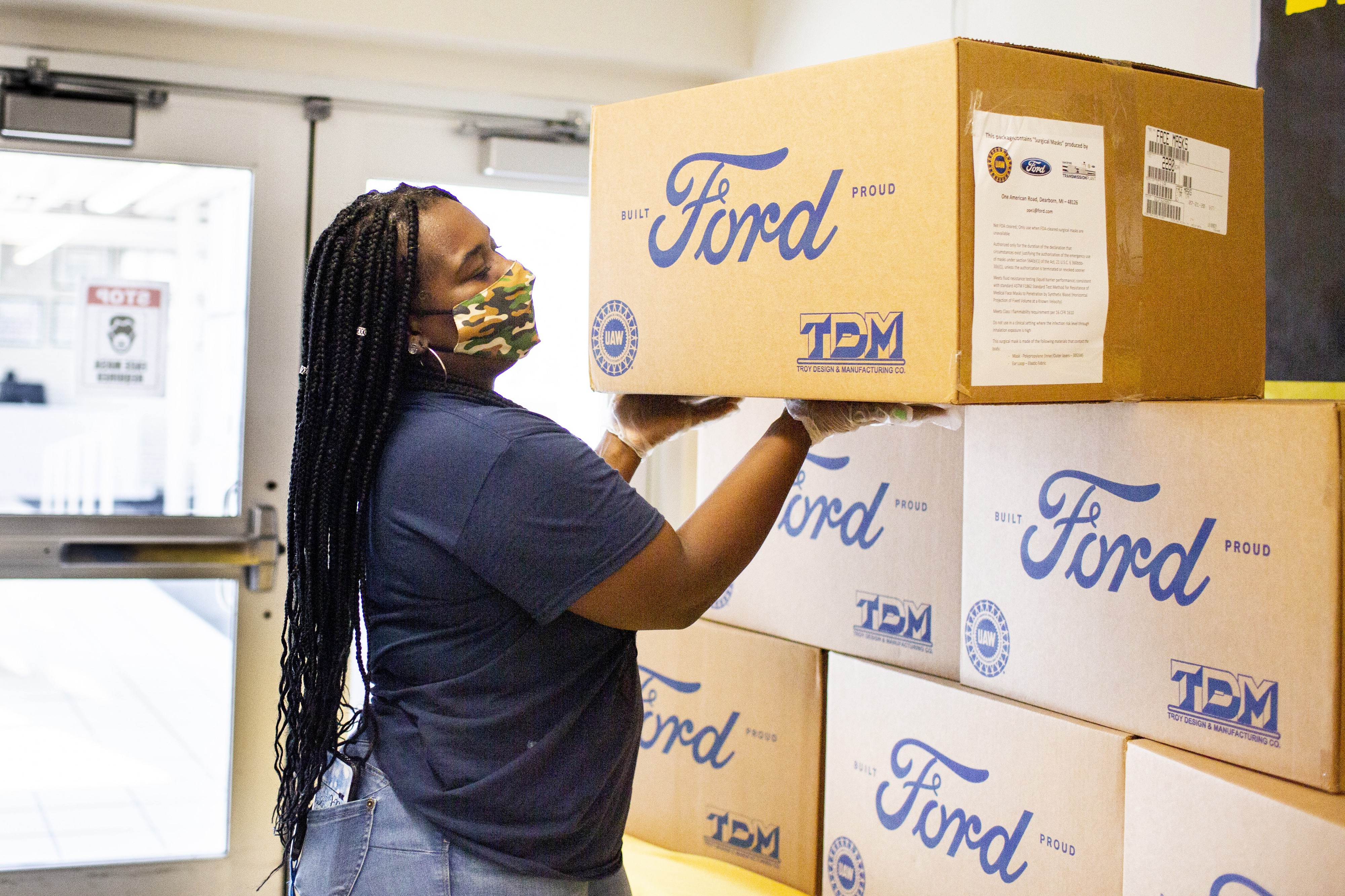 Female Ford employee inspecting Ford boxes