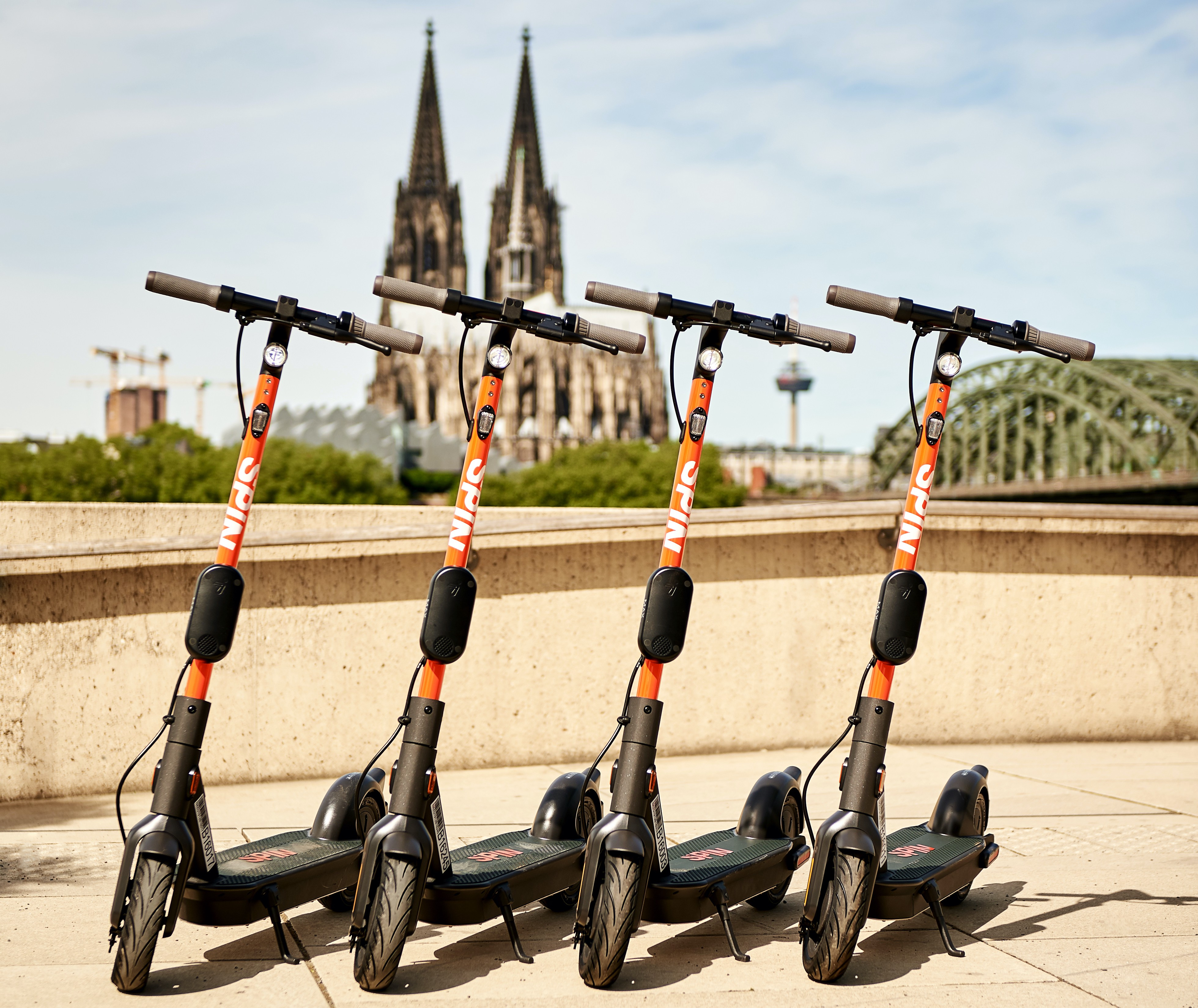 Four Spin scooters sit in front of the cathedral in Cologne