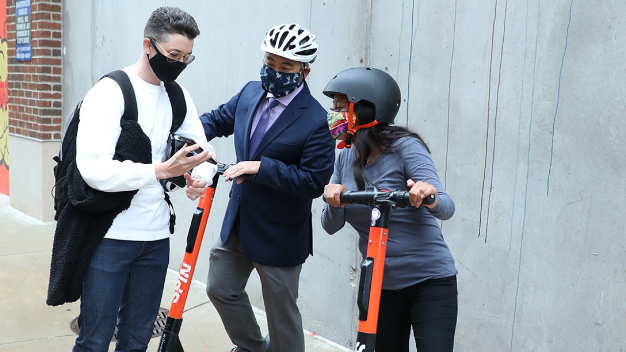 Man showing phone to two Spin scooter riders