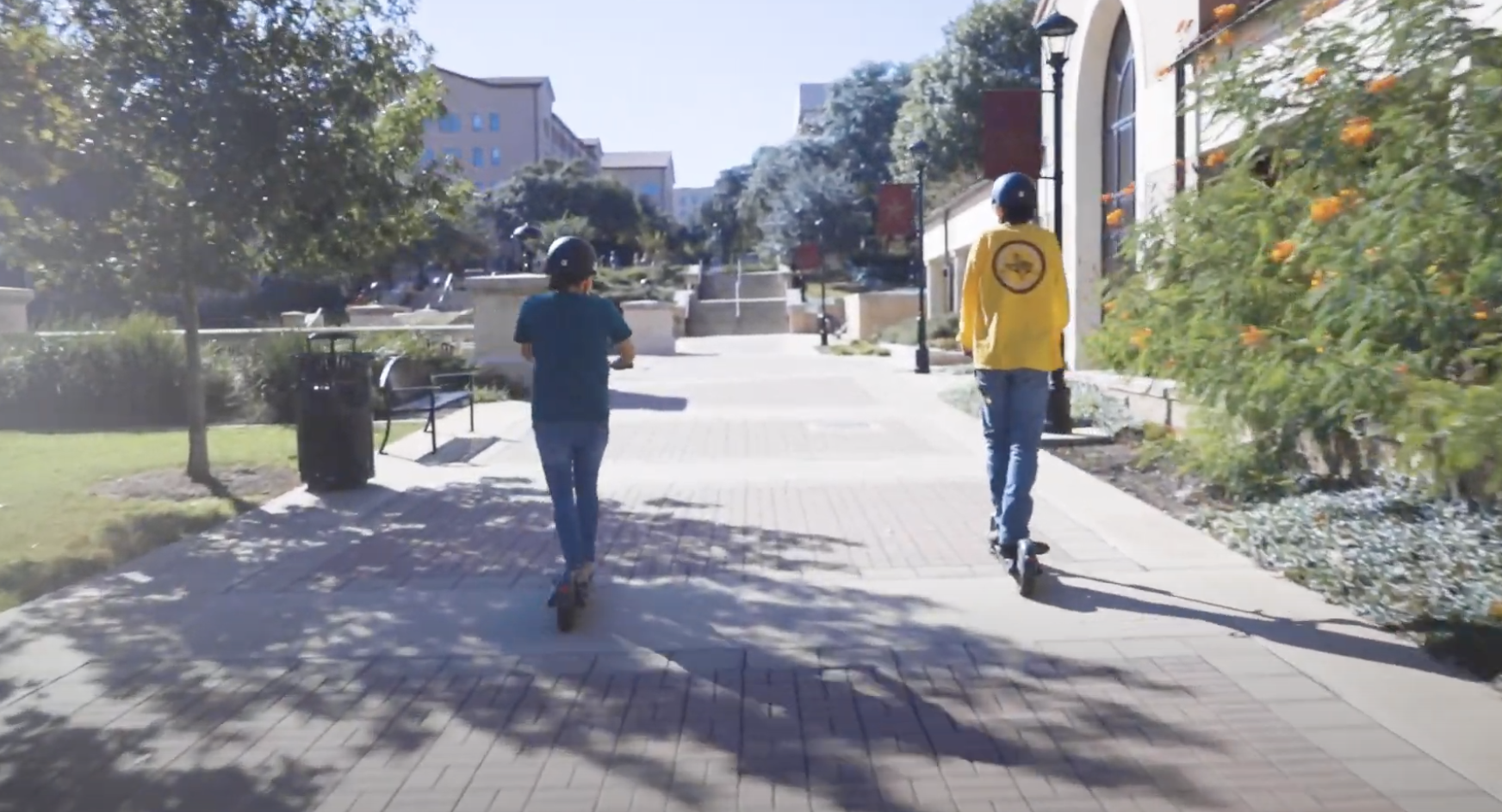Students riding scooters at Texas State University campus
