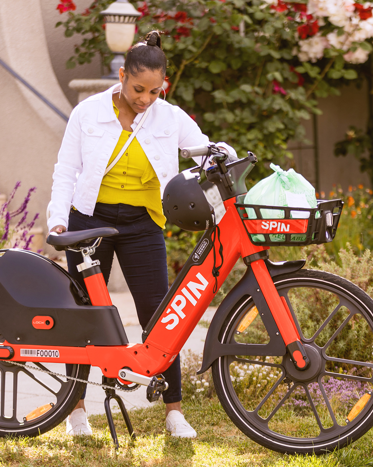 A young woman stands next to a Spin e-bike, with a helmet hanging on the handlebars and a bag in the front basket.