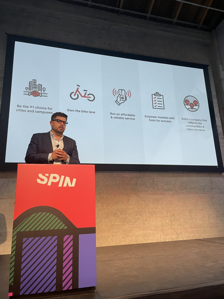 Spin CEO Ben Bear stands behind a podium at a speaking engagement with images representing Spin's five pillars.