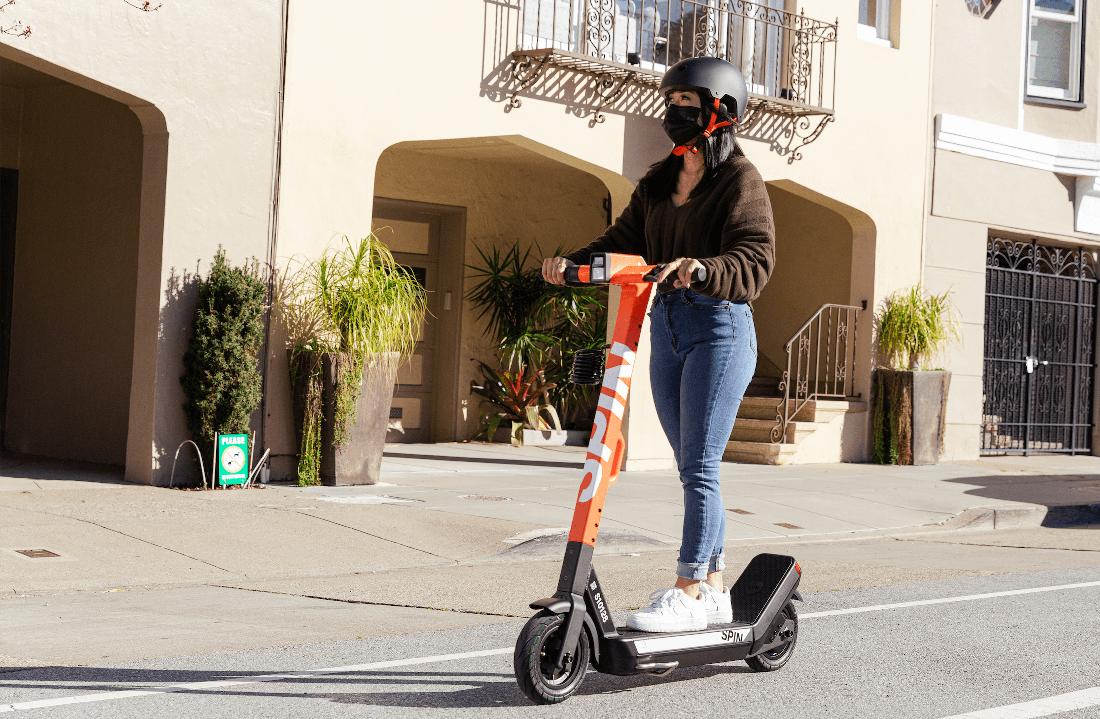 A woman wearing a helmet and face mask rides a Spin S-100 T scooter.