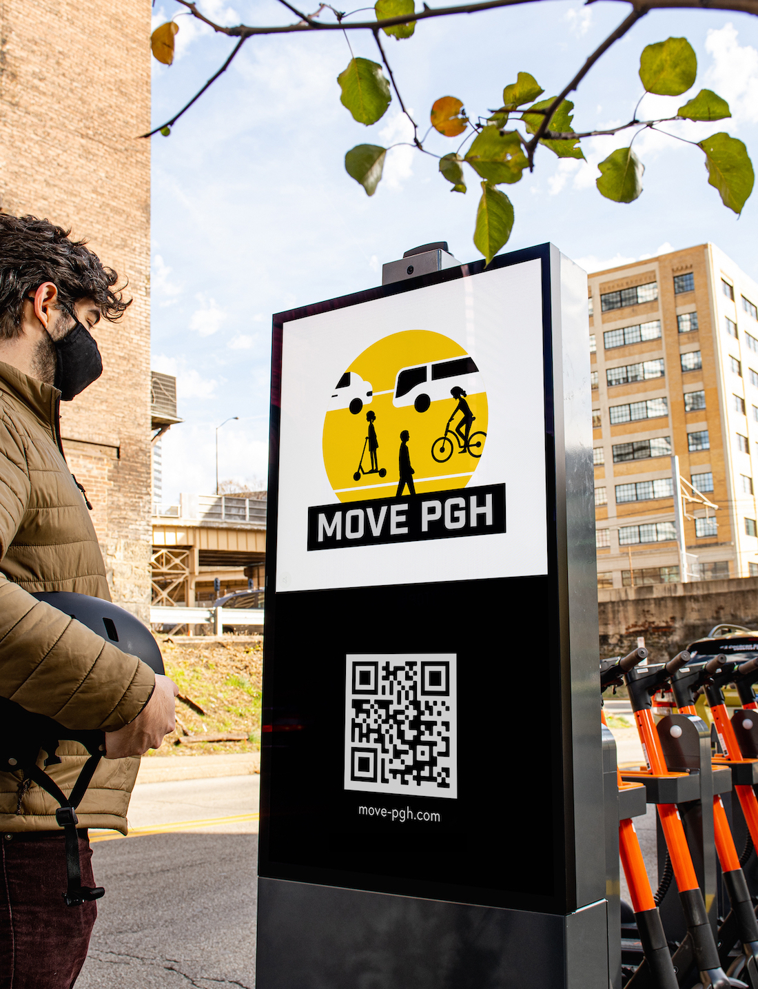 """A man looks at a sign on that says """"Move PGH."""" The sign is attached to a scooter charging station with several scooters parked in it."""