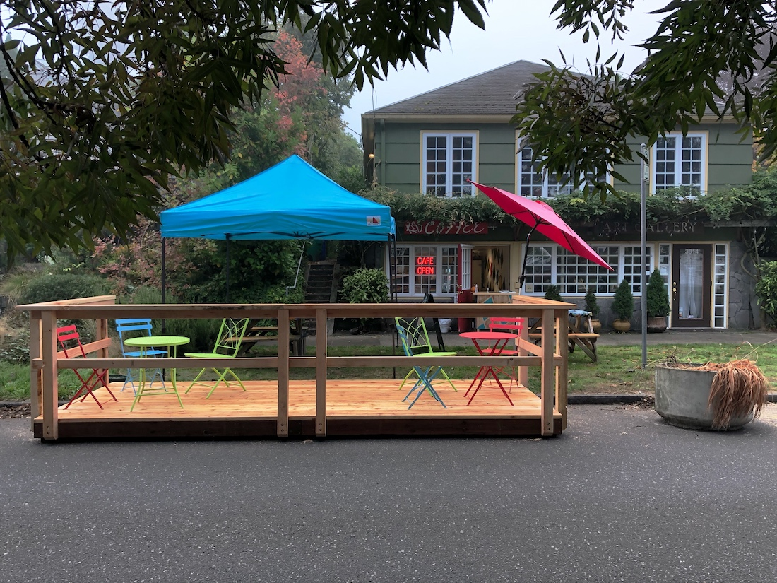 Outdoor seating in front of a cafe, including multi-colored chairs and umbrellas.