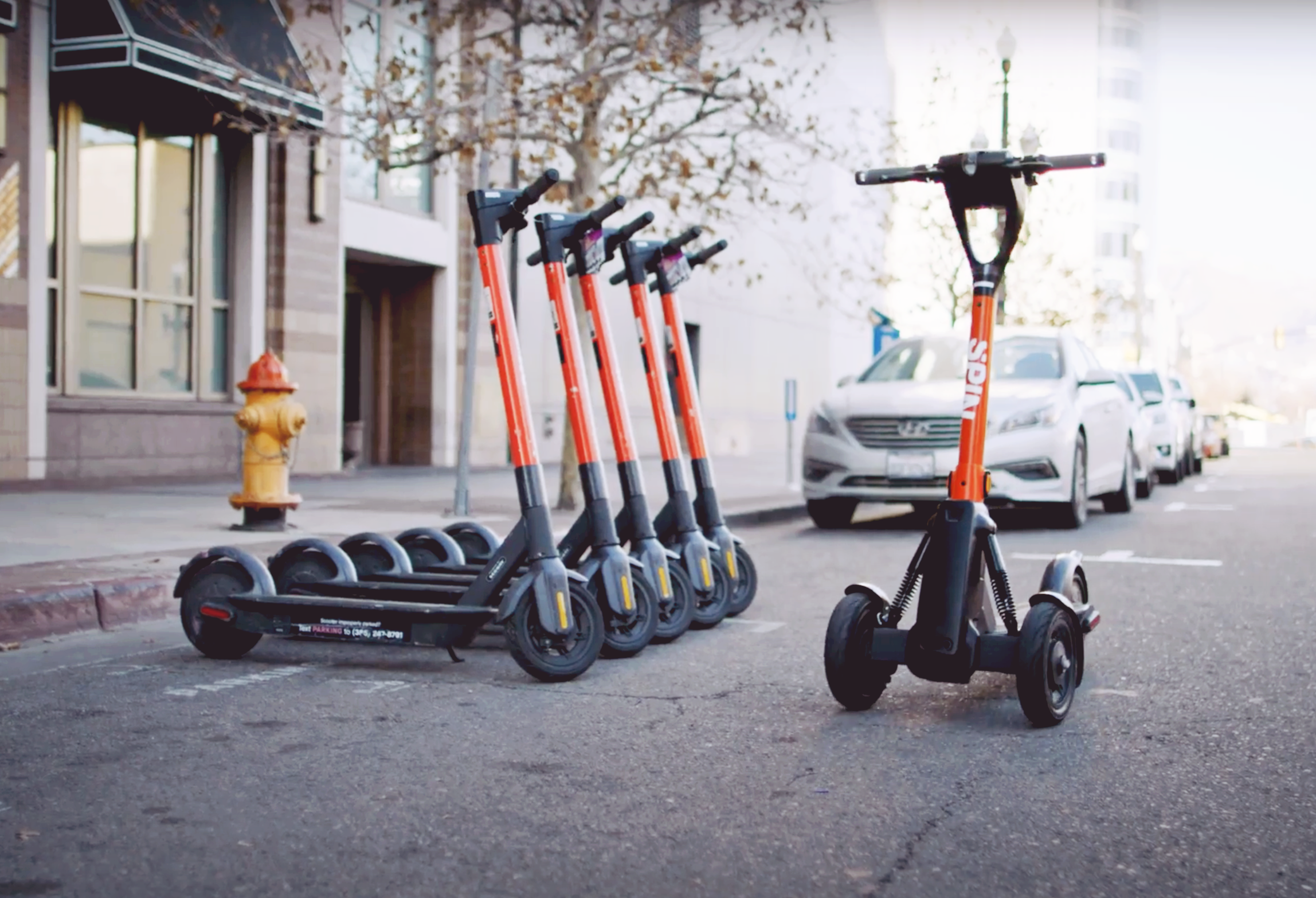 A three-wheeled Spin scooter in front of a row of original two-wheeled Spin scooters.
