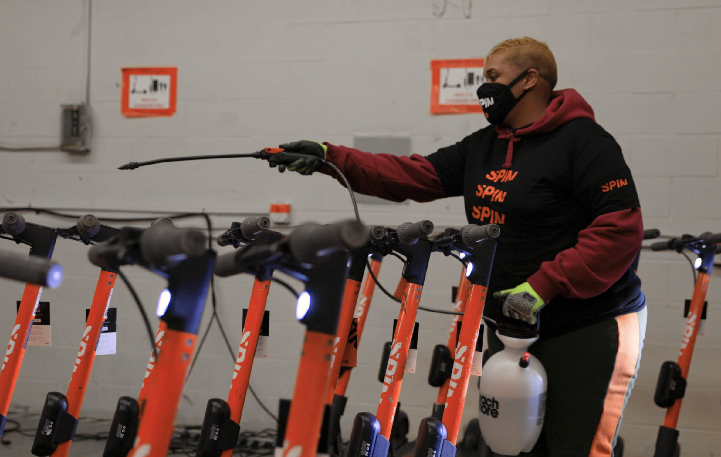 Rubie, wearing a mask, sprays Spin scooters in the warehouse with disinfectant.