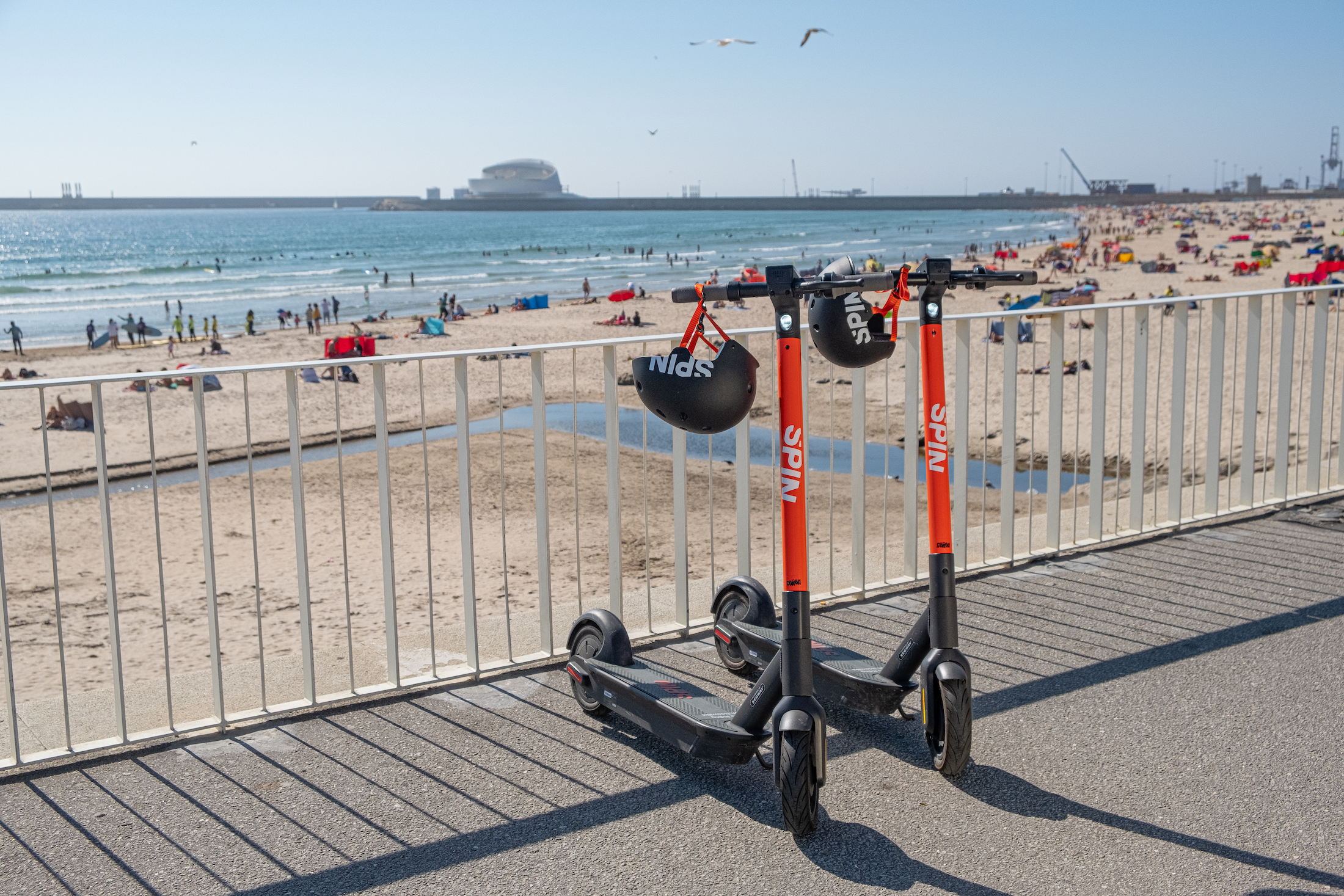 Two Spin scooters with helmets hanging from their handles are parked in front of a beach.