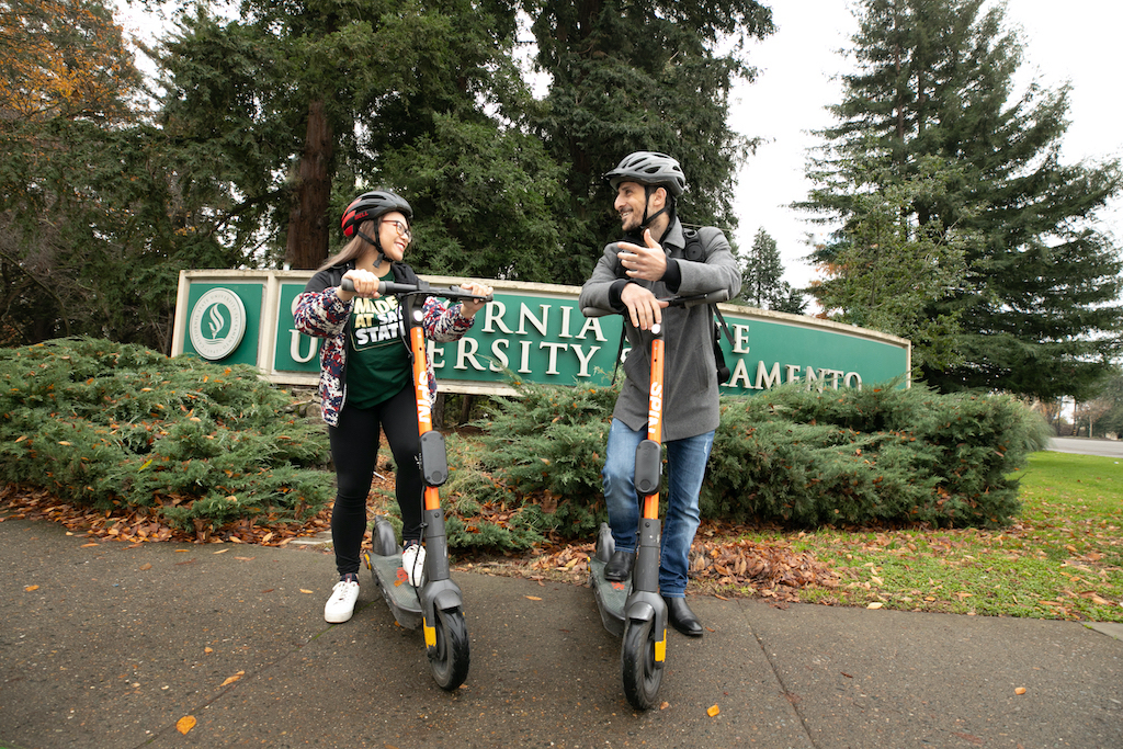 Two students stand with scooters in front of a sign which reads Sacramento State.