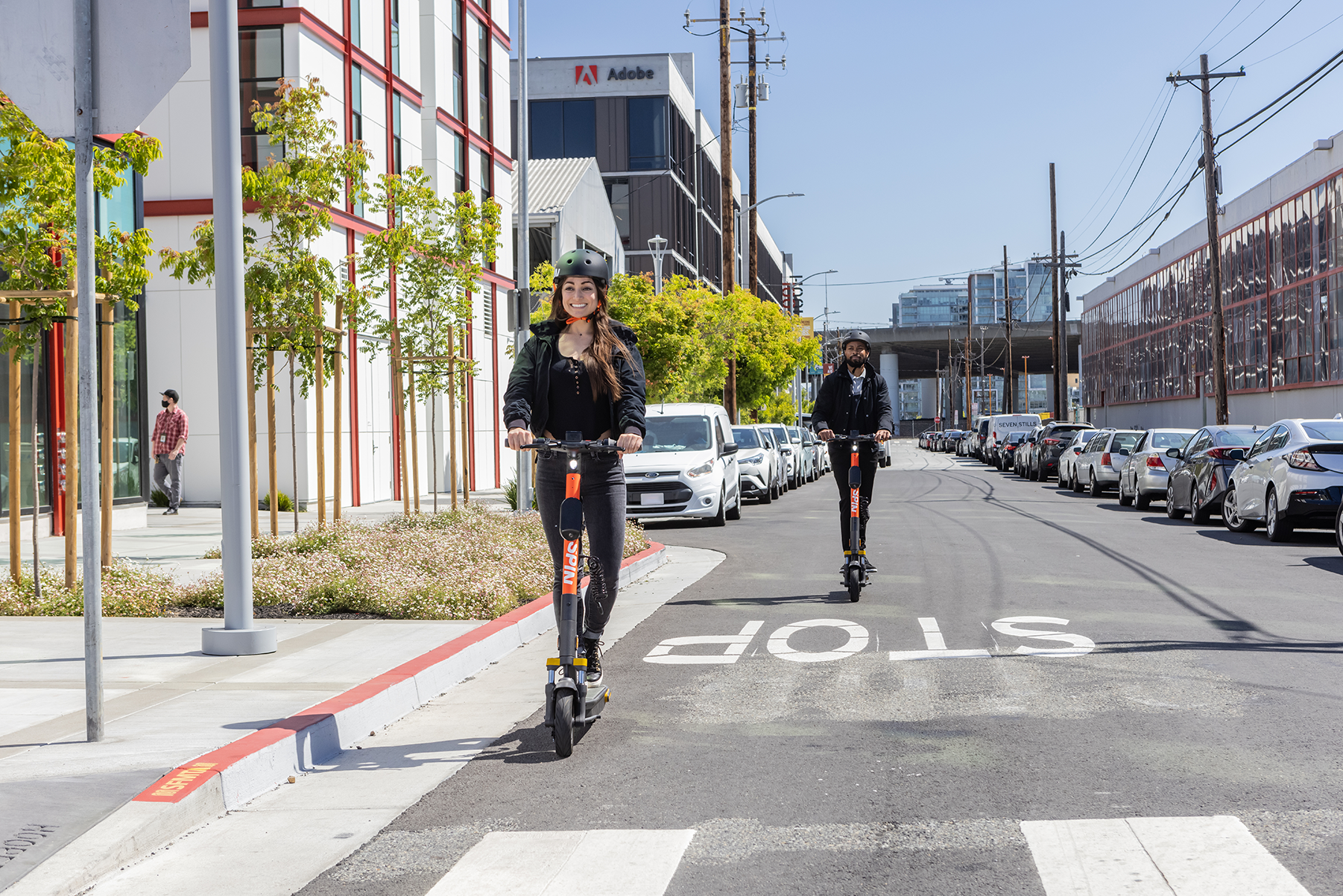 Two people wearing helmets riding e-scooters in the streets.