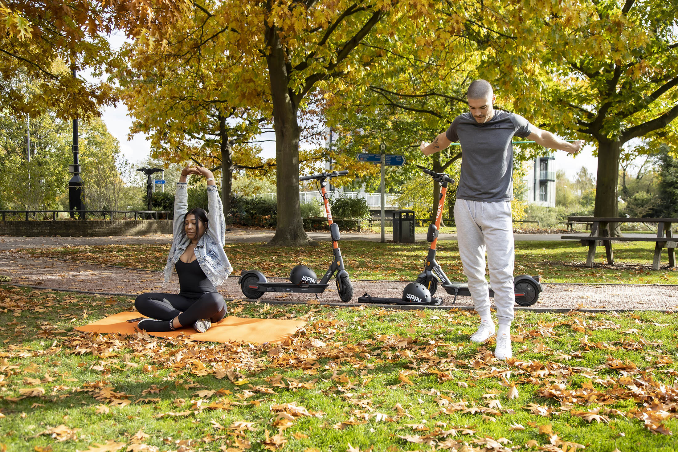 A man and a woman stretch on the grass in a park with two scooters behind them