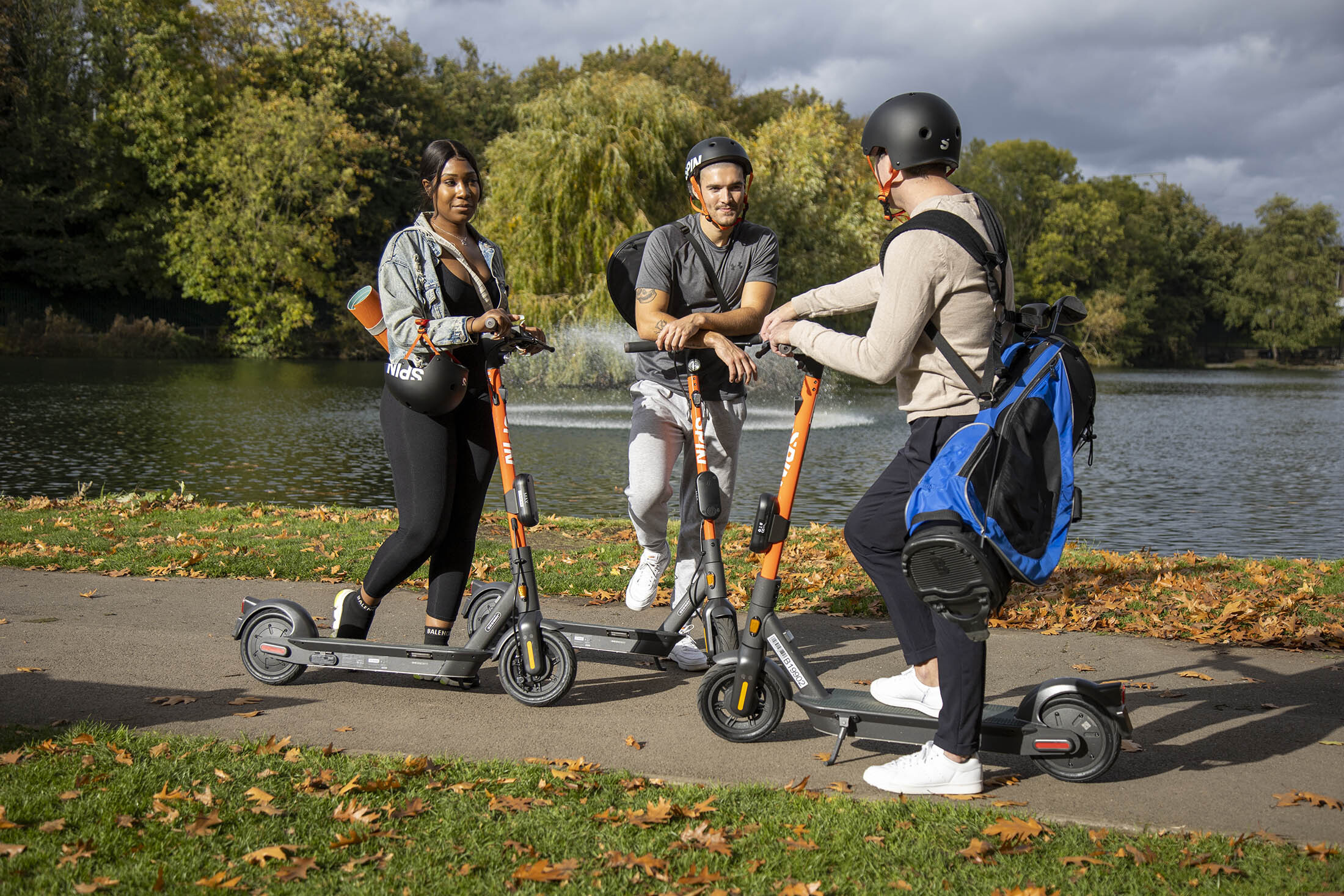 Three people wearing helmets and standing on scooters chat in a park near a lake.