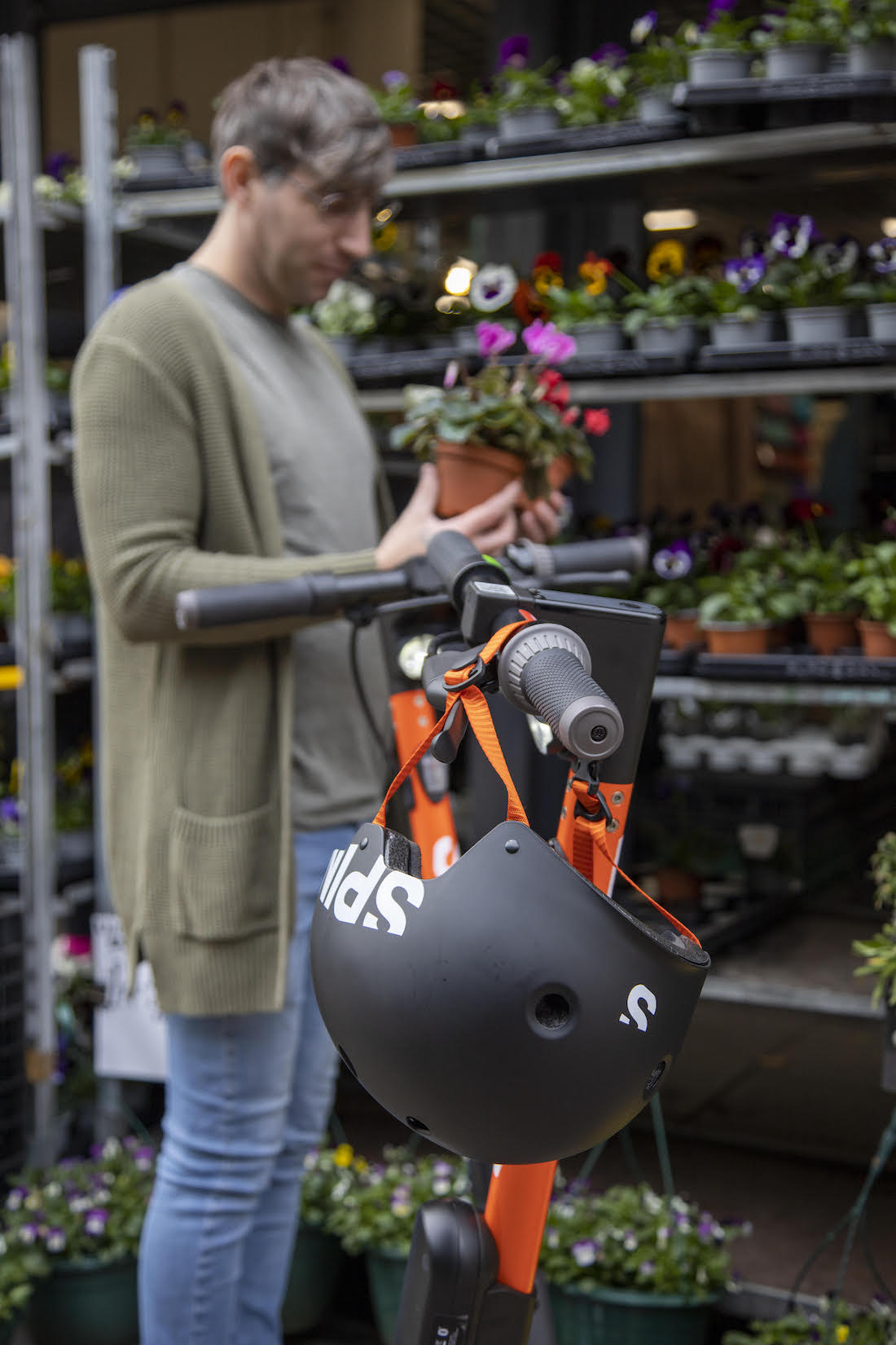 A scooter with a helmet in front of a man shopping for flowers.