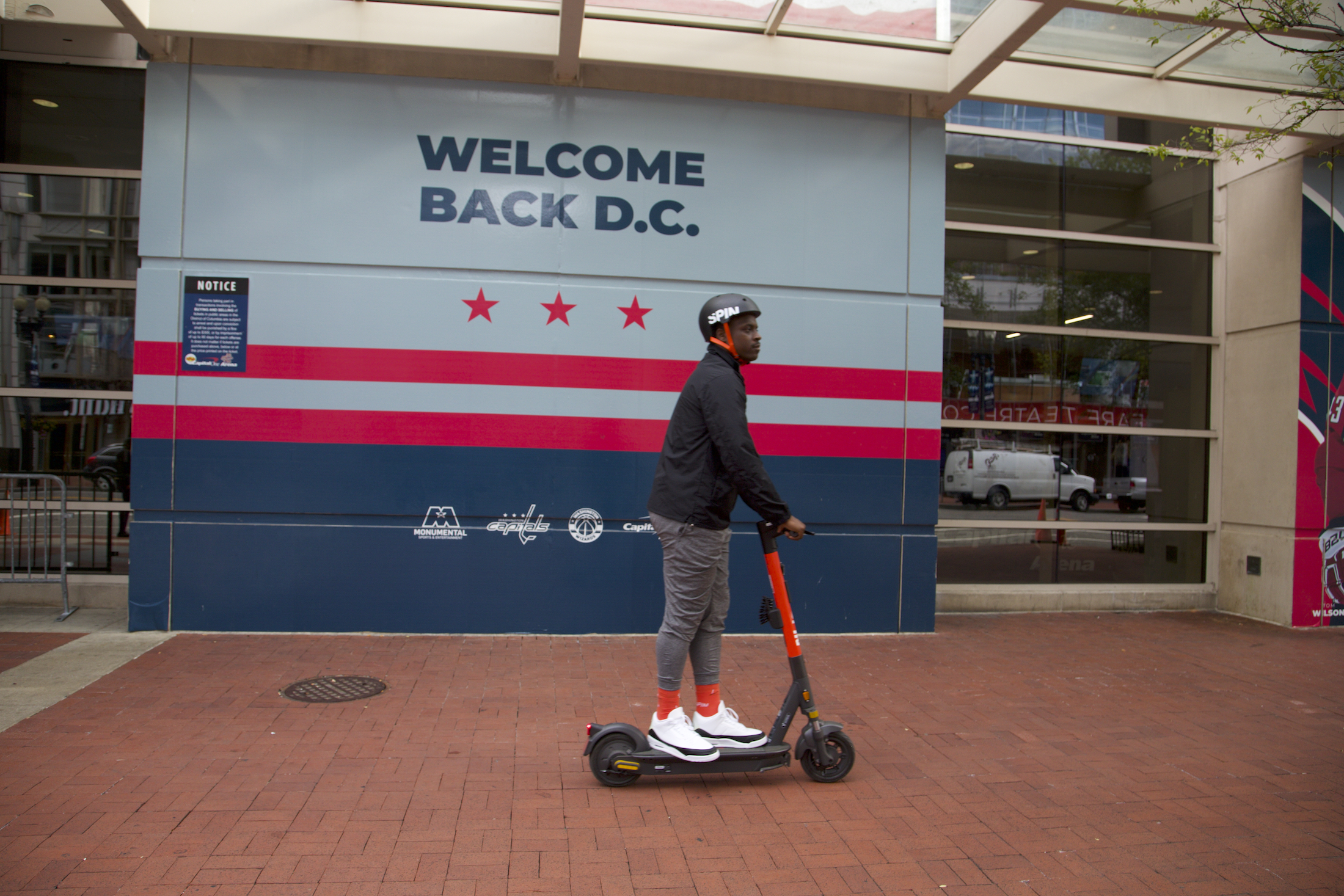 """A man riding a scooter while wearing a helmet in front of a mural that says, """"Welcome Back D.C."""""""