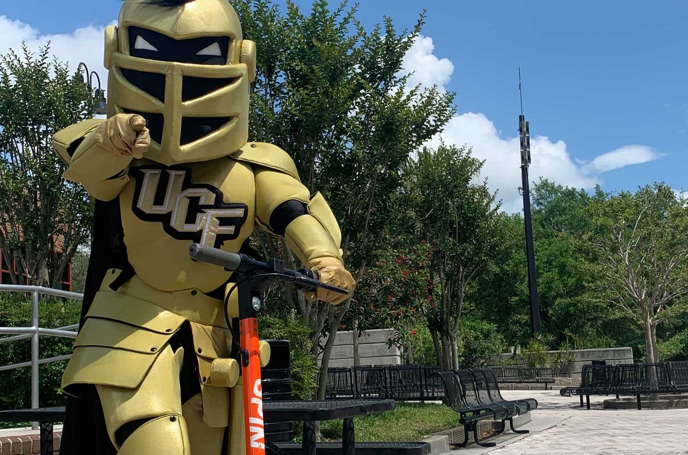 A person dressed as a knight mascot for University of Central Florida stands on a scooter, pointing toward the camera.