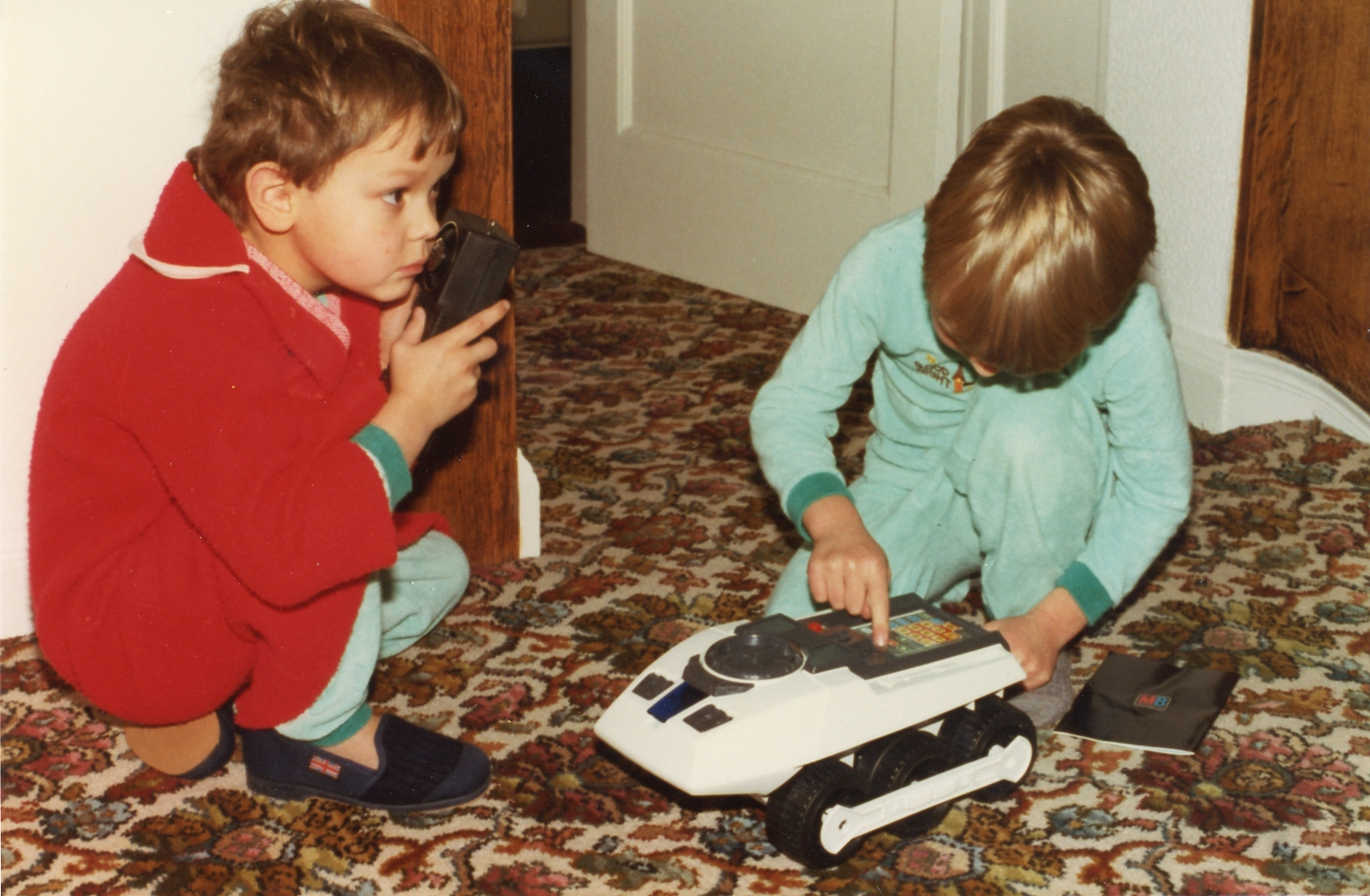 An old scanned photograph showing two boys playing with a new present.