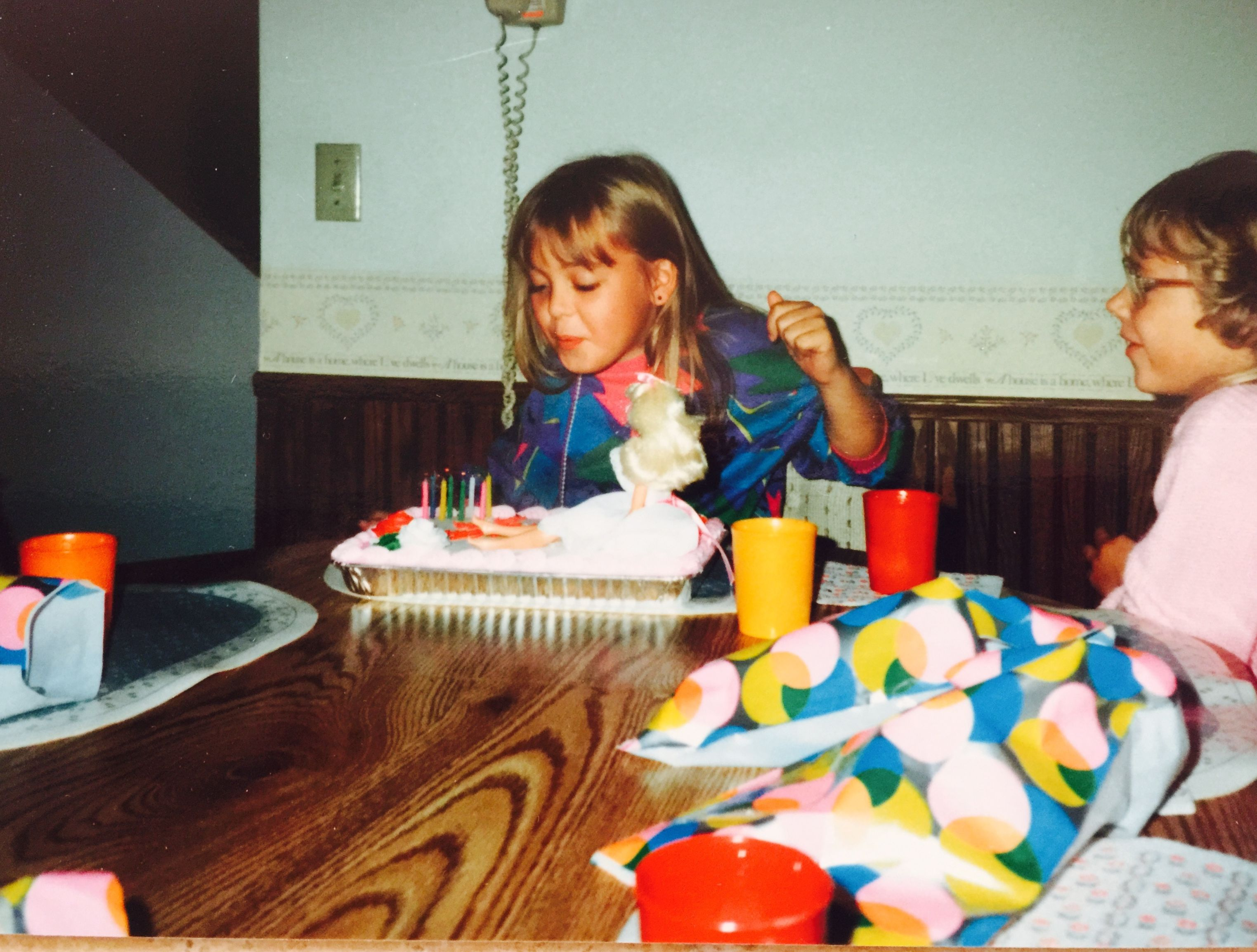 Scanned image of an old photo showing a girl blowing out the candles on her birthday cake.