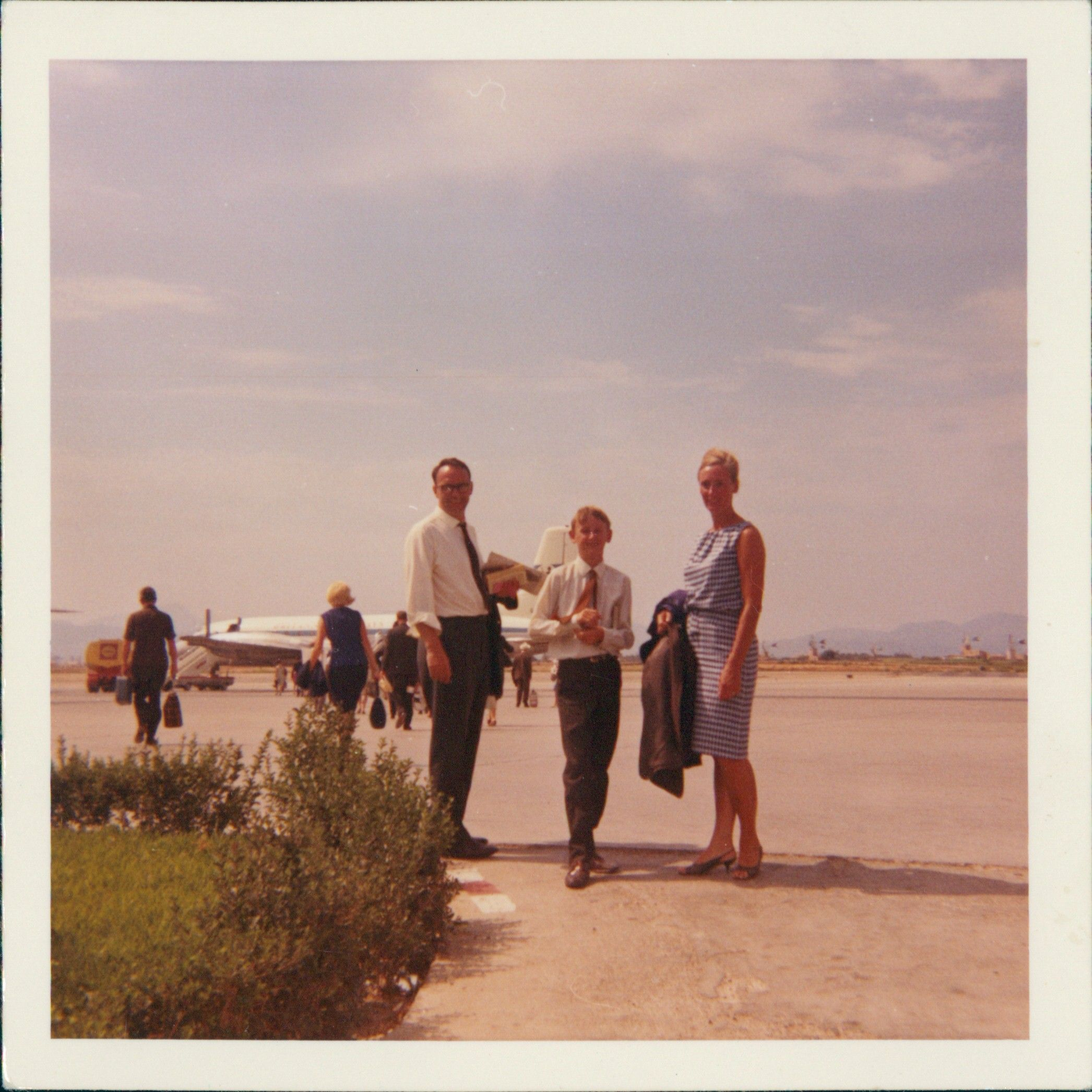 Digitised image of an old photo from the 70s showing a family on the tarmac at an airport.