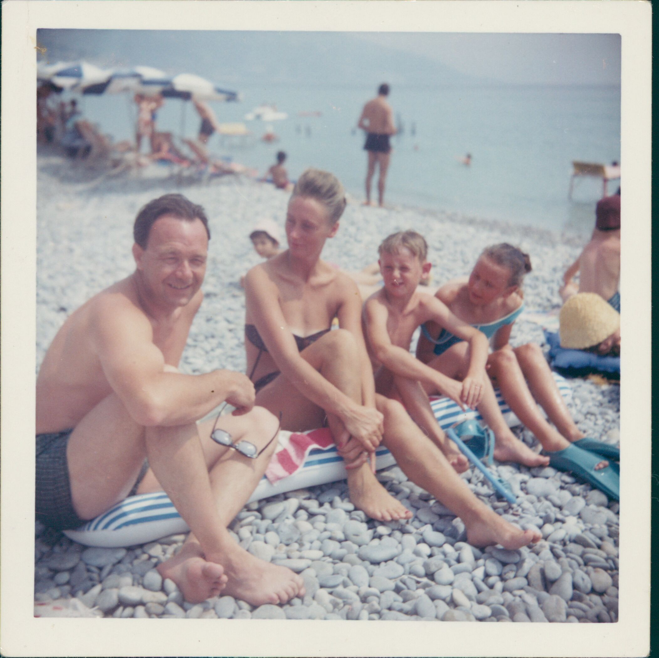 Scan of an old photograph showing a family enjoying a day at the beach.