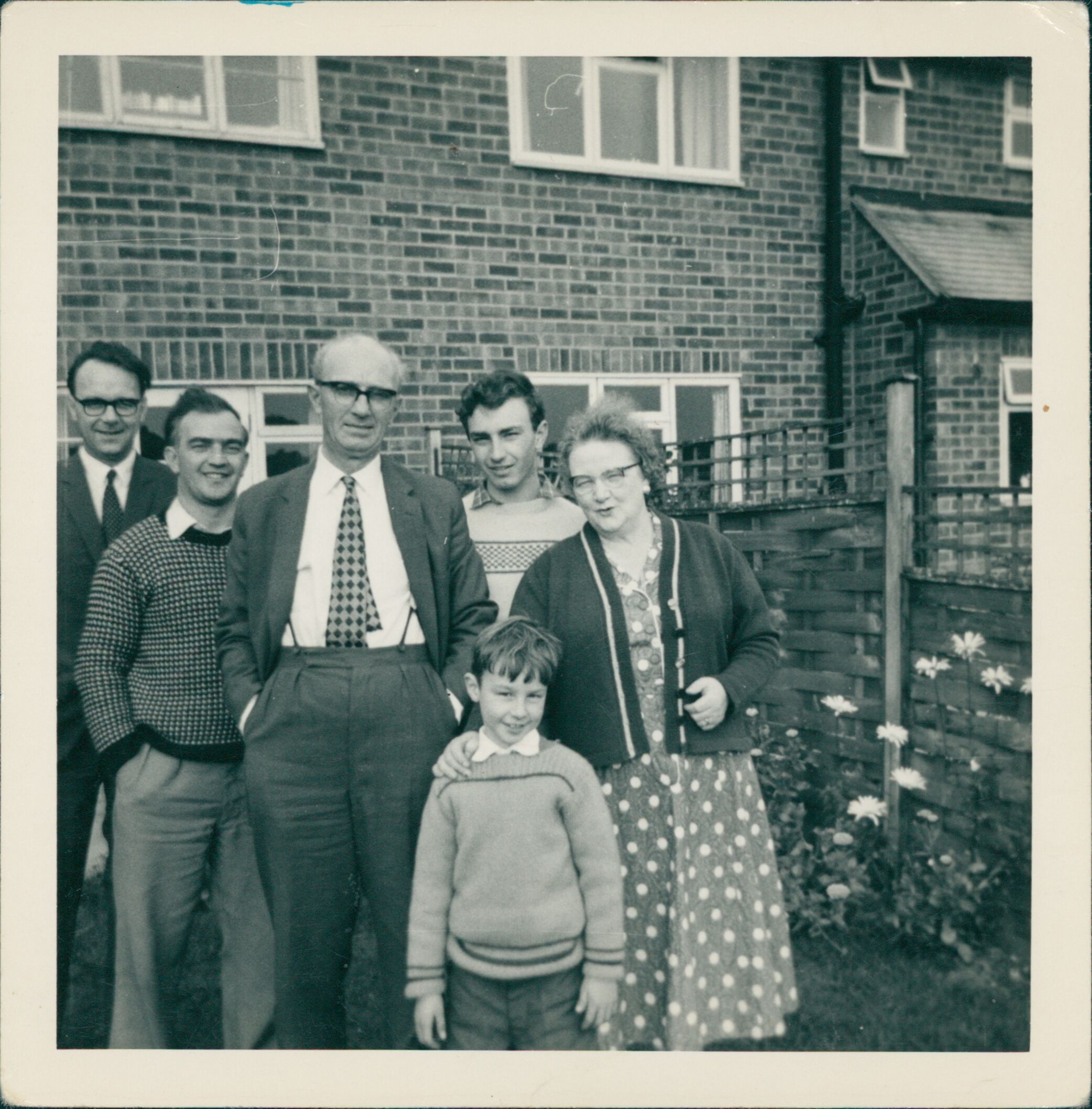 Scanned photo depicting a family posing for a photograph in their garden.