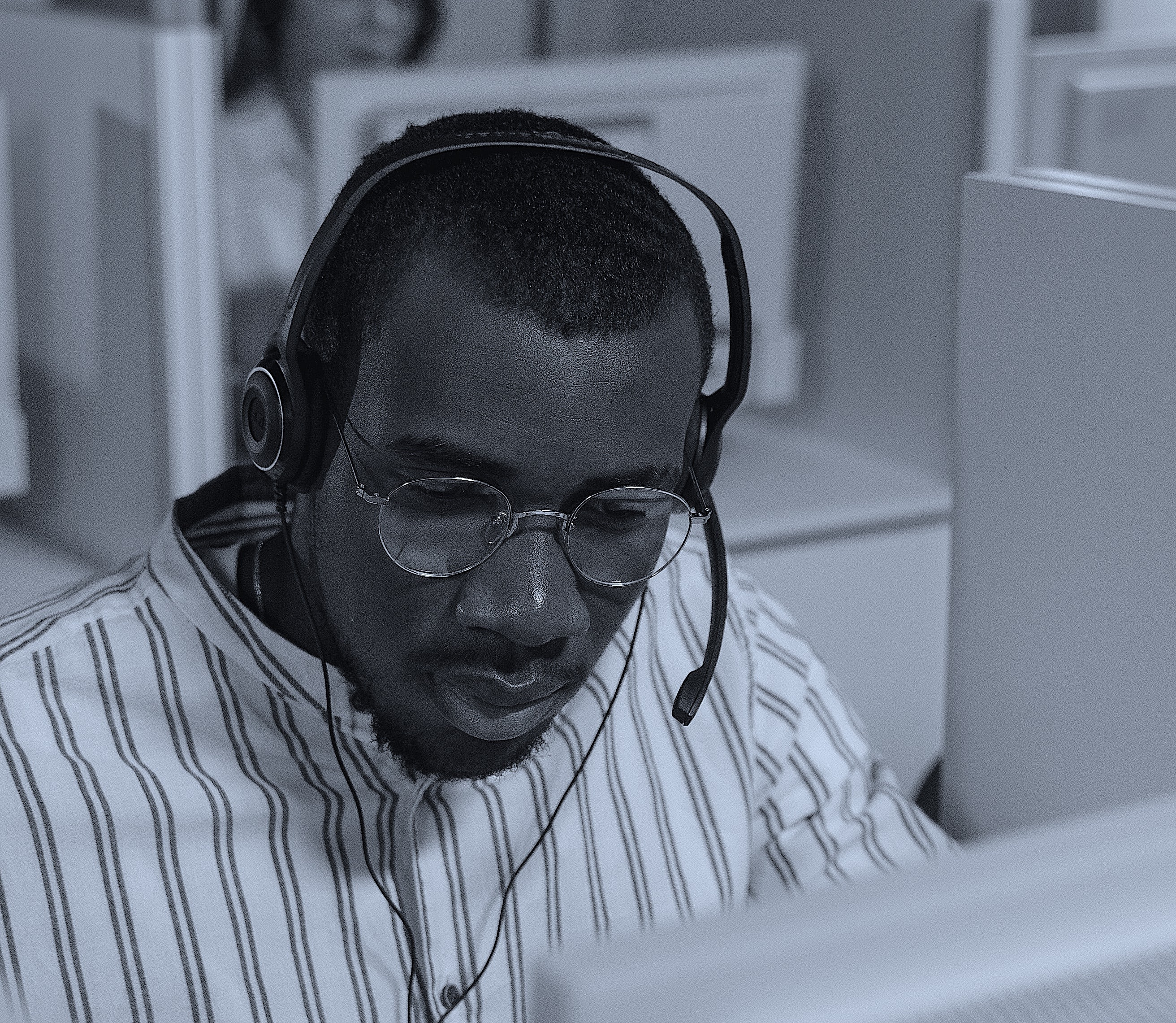 Man with glasses wearing glasses and looking at a computer.