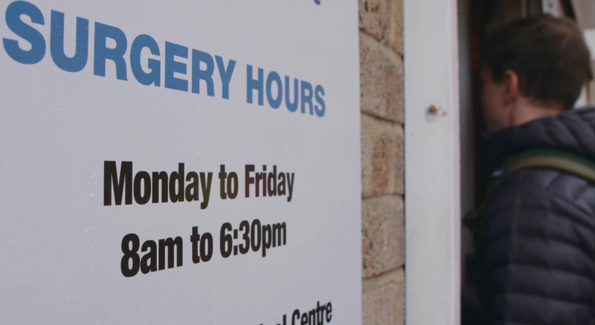 A GP practice with a sign showing its opening hours.