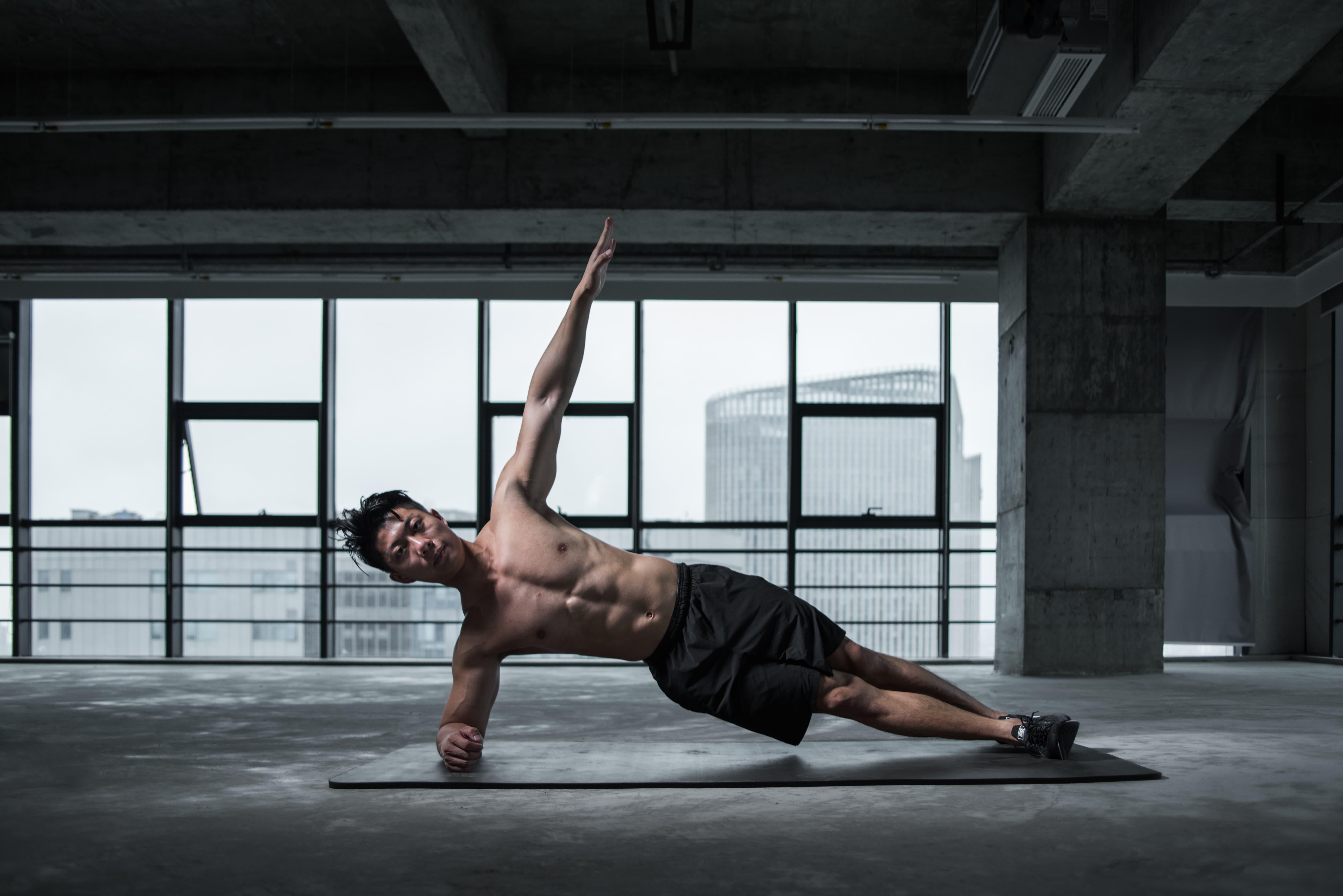man in side plank position